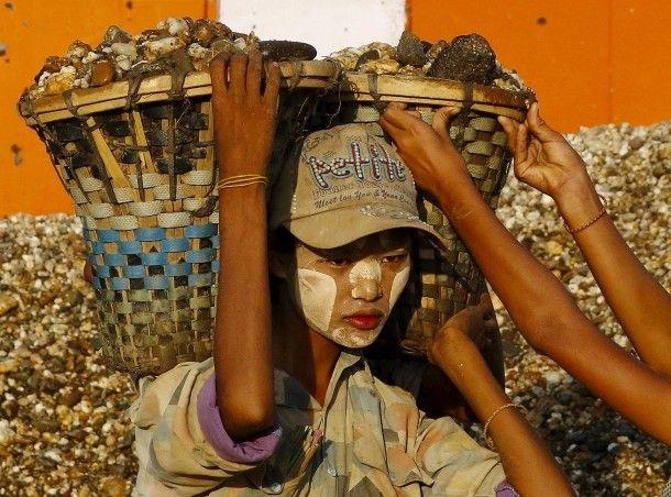 12. November 2015. Eine schwere Last hat die junge Frau in Dala, einem Township gegenüber Rangun in Burma, zu tragen. Der Kies wird mit Booten transportiert, die Entladung ist Handarbeit.