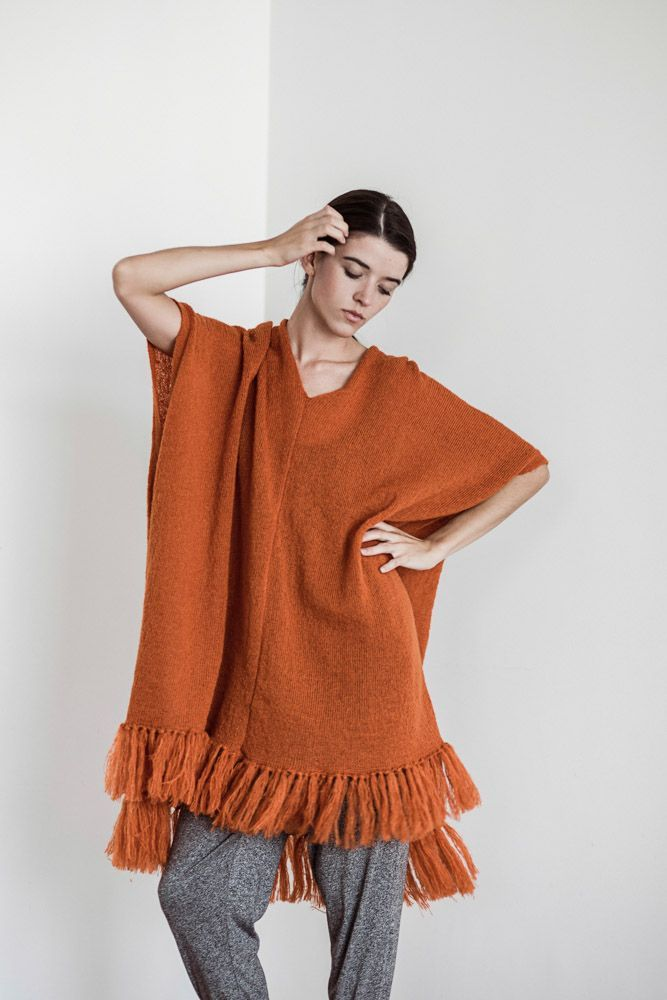 The 'Eddir Poncho' by @julia.de.jong is the perfect piece for layering or to wear as is. Available in orange or black at melko.com.au.