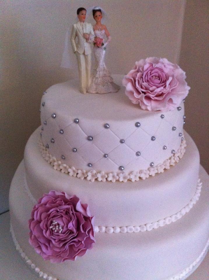 Nydelig bryllupskake i 3 etg med håndlagde peoner i sukkerpasta. Dette er en sjokoladekake med sjokoladekrem og vaniljekrem. Pris 3900,-
