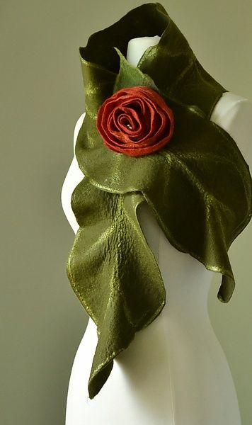 """Rebecca Scarf in Deep Green, Red Rose"" Created by Elizabeth Rubidge One of a Kind 100% wool scarf with silk fiber accents has a softly draped leaf shape. Scarf is held in place with a hand felted and rolled scarlet rose pin."