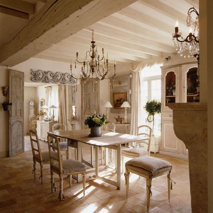 Salle à manger blanche et énigmatique avec carrelage de sol en pierre, table et chaises en bois, lustres vintage et placard blanc