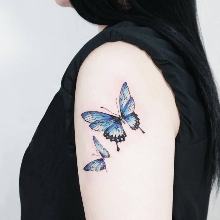 Blue butterfly tattoo on the left upper arm.