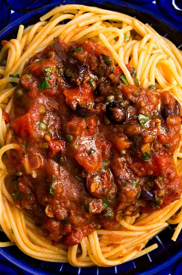 Easy Pasta Puttanesca!  A classic Italian pasta sauce based on pantry items such as olives, capers, anchovies and canned tomatoes. Perfect for a quick weeknight dinner. On SimplyRecipes.com