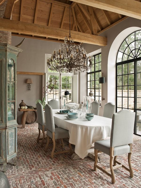 Stunning!  I love the glamor of the chandelier and high ceilings with the rustic feel of the brick floors and distressed cabinet.  All the natural light does wonders, too.: