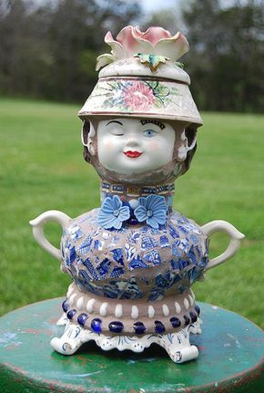 The mid section is a lamp body. The base is a ceramic base for ???? I don't know what. The head is a metal ball- a plumbing float?? The face is from a Bailey's cup, The hat body is an upside down cracked bowl and the top is a chipped candel holder. The blue flowers are junk earrings