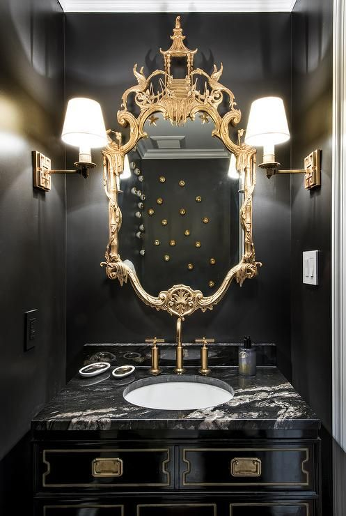 gold and black powder room boasts walls painted bold black lined with a gold chinoiserie mirror