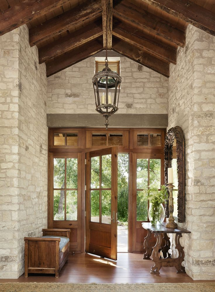 Natural stone walls, exposed wood beams, vaulted ceiling, wood front door, lantern pendant lighting, wood bench, large mirror | Ryan Street & Associates