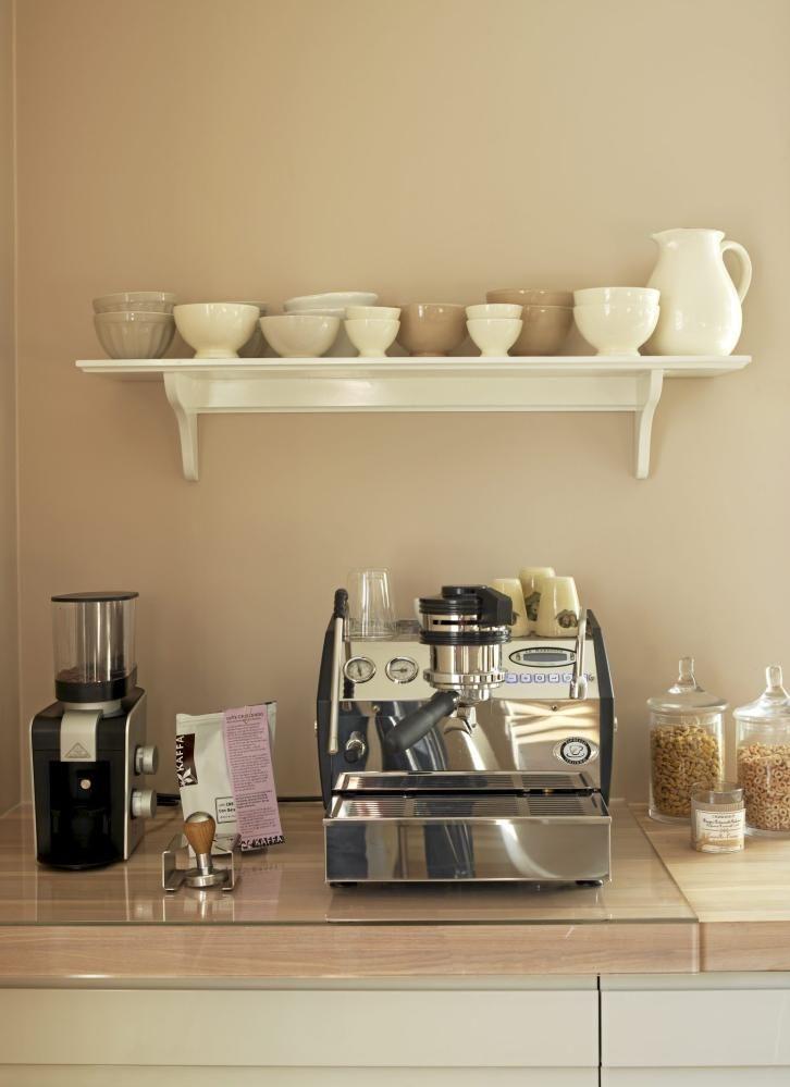 En glassplate er lagt på kjøkkenbenken under espressomaskinen for å unngå at kaffesøl skal skape stygge flekker i treet. På veggen over henger en hvit hylle med søte skåler i hvitt, beige og brunt.