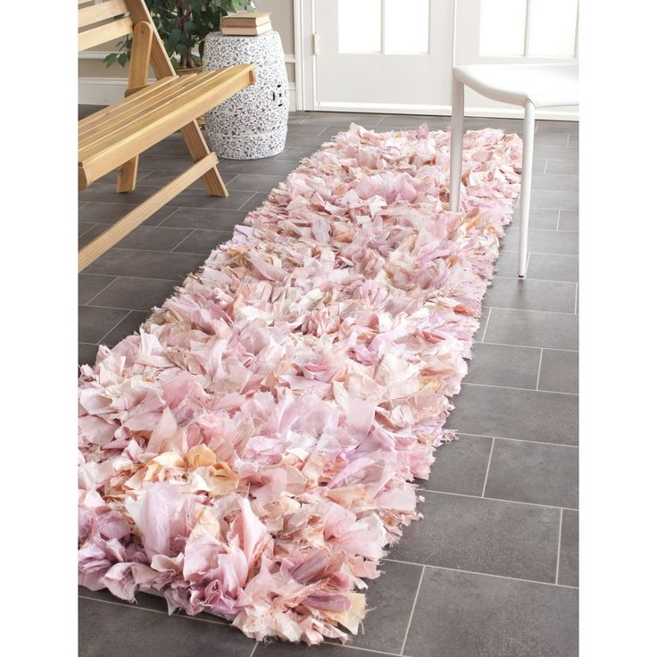 The Safavieh hand-woven pink shag rug brings texture and delicacy into any room. With a luxuriously deep two-inch pile, a wide, loose fabric weave, and varying soft shades of pink and peach, this rug is like a strip of soft rose petals.