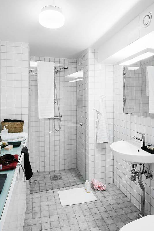 Wnęka wyposażona w szklane drzwi stała się funkcjonalną kabiną prysznicową. Zrezygnowano w niej z brodzika, dzięki czemu łazienka wydaje się większa. Całą jedną ścianę zabudowano nowoczesnymi szafkami do przechowywania, zaopatrzonymi w praktyczny szklany blat.