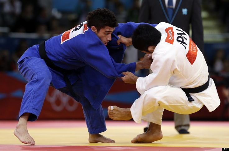 Hiroaki Hiraoka of Japan competes against Ashley McKenzie of Great Britain (in blue) during the elimination round of the men's 60kg judo competition at the 2012 Summer Olympics, Saturday, July 28, 2012, in London.