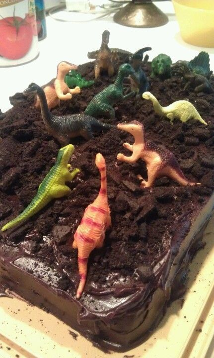 Dinosaur birthday cake- chocolate cake, chocolate icing, crumbled oreos for dirt, & dinos on top! :) I could do parts in green icing and green coconut for grass...and add whoppers etc for bolders