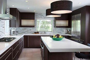 Světla s tmavými stínidly doplňují spolu s tmavými dvířky skříněk kompletní vzhled kuchyně a tvoří její středisko.