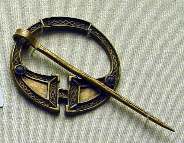 Copper alloy pseudo-penannular brooch with panels of angular interlace; blue glass cabochon set near each expanded terminal; pin.