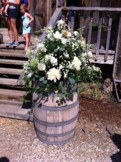 Rustic white wedding arrangement on wine barrels #santaynezvalleyflorist #figueroamountain #farmhouse #winecountry #dahlia #wedding #ceremony