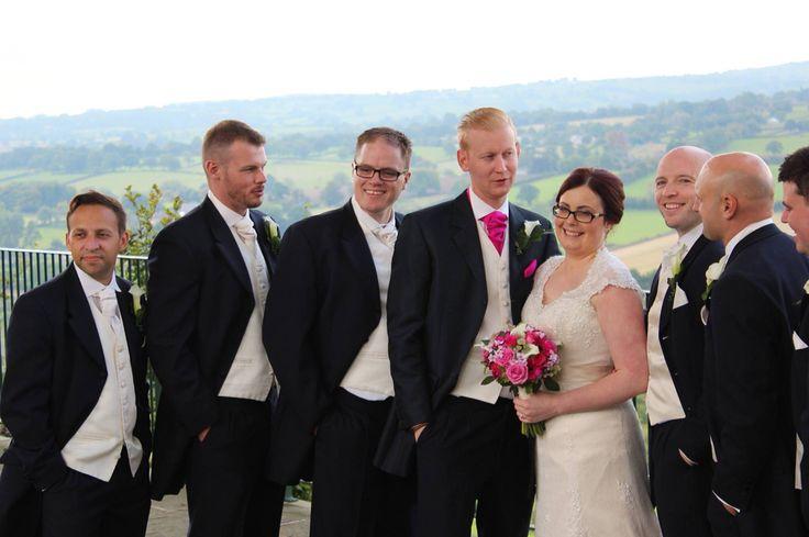 Navy wedding suits, cream and gold striped waistcoat, ushers in cream cravats groom in raspberry.