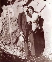 Bonnie & Clyde standing next to a Route 66 sign in Missouri.