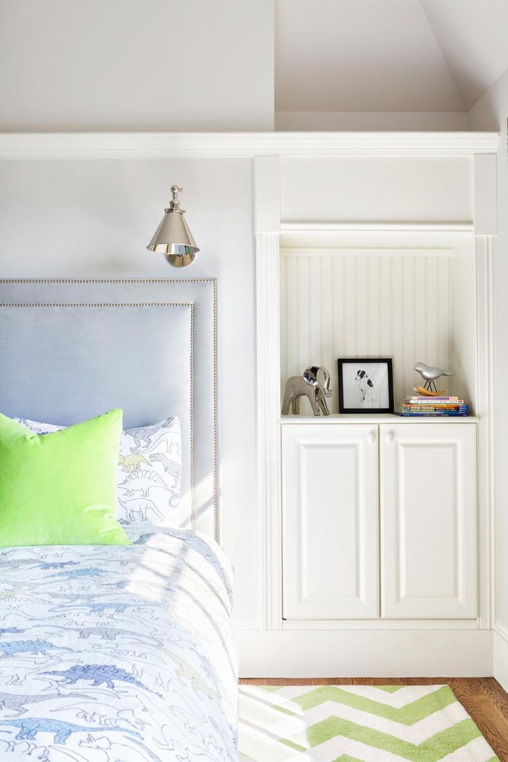 A built-in nightstand backed by decorative beadboard provides stylish, functional storage in this transitional kid's bedroom. An upholstered headboard with two rows of nailhead trim is custom-built to fit the space, and reading lights above are a practical addition. Dinosaur-printed bedding, acid green pillows and a matching chevron rug add kid-friendly flair.