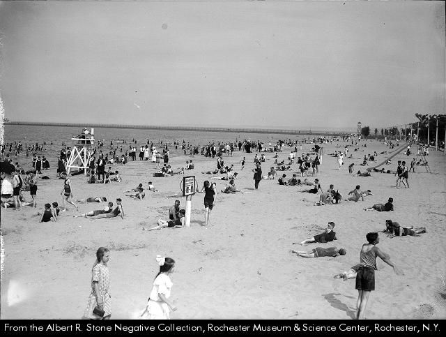 People on the beach and in the lake at Ontario Beach Park in Rochester NY. A lifeguard sits on a high stand at the edge of the water, at left. There is a slide at the far right. In the center, a sign gives the bath house hours and the temperature.
