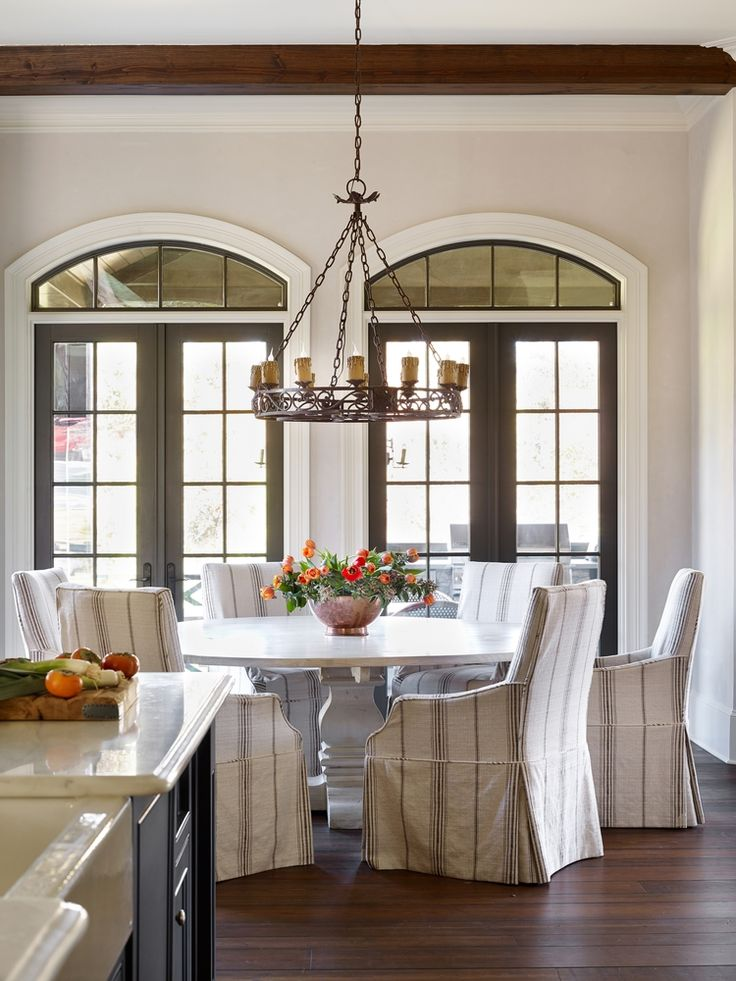 French Dining Room Features Stained Box Beam And An Iron Candelabra  Illuminating A Whitewashed Round Dining Table Surrounded By French Striped  Dining Chairs ...