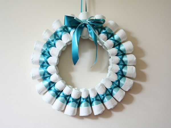 Rolled Diaper Wreath Instructions - My clever daughter-in-law made one of these for a baby shower and sent the link to me!  It is really cute!
