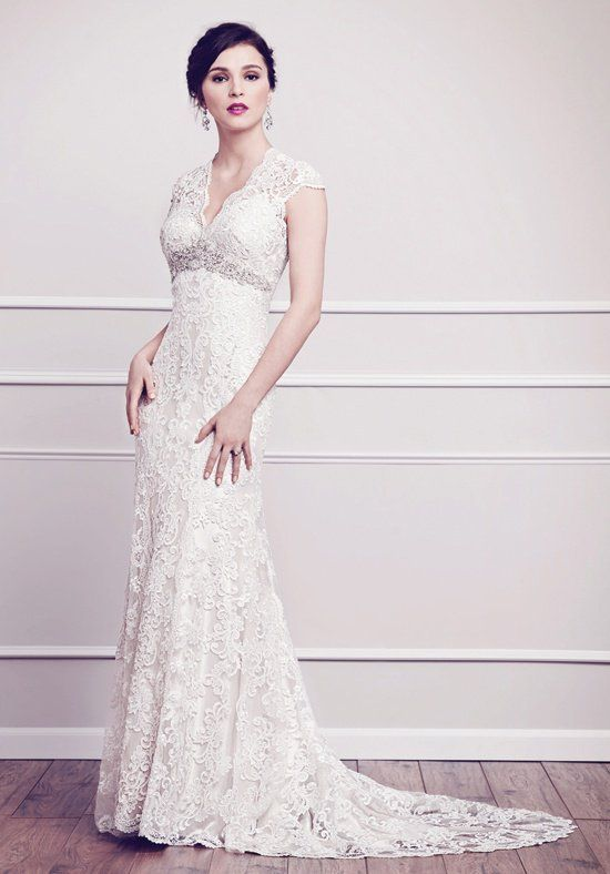 Classic V-neckline gown wrapped with floral arrangements made of Venice Lace creating a bold contrast finishd with heaviy beaded arch of jewels and crystals. Zipper back.