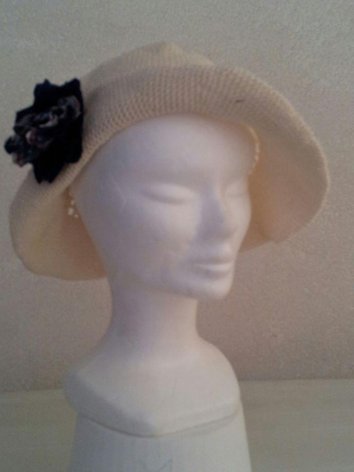 cappello realizzato ad uncinetto con spilla realizzata in tessuto
