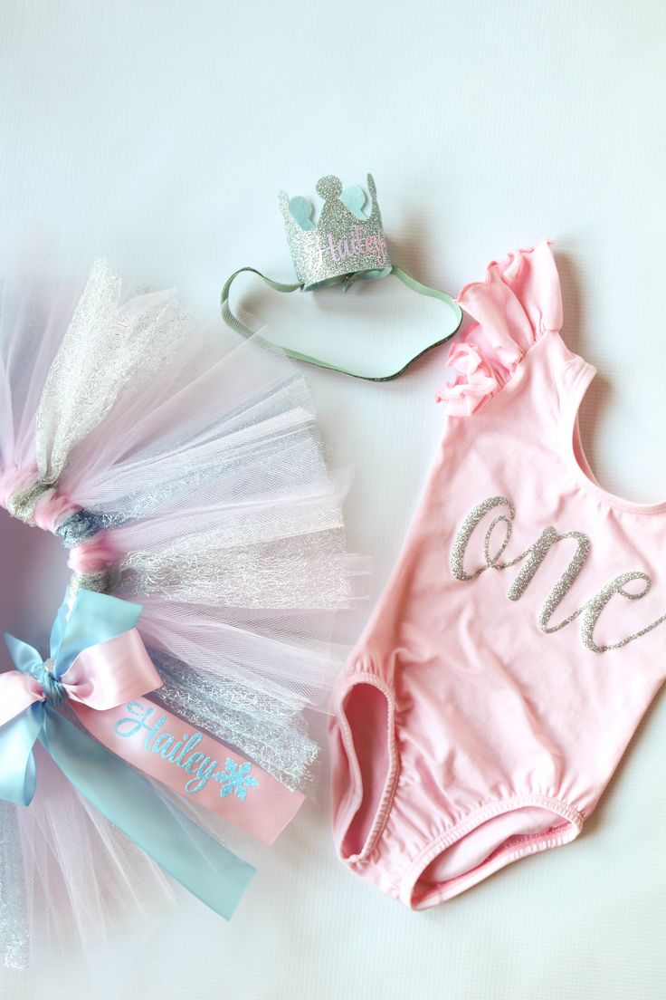 First birthday personalized cake smash winter onederland outfit in pink, silver, and light baby blue for baby girl's 1st birthday party.This  3 piece perfectly coordinated set comes with fluffy birthday sparkling birthday tutu with bow sash, glitter silver pink leotard, and a silver crown.