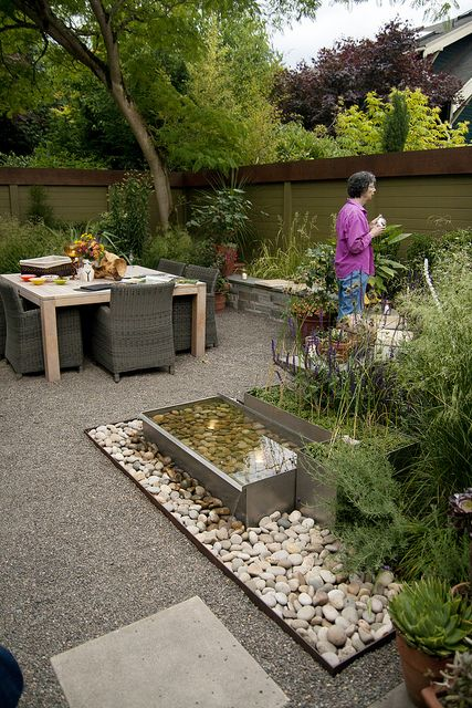Beautifully divided small garden spaces with gravel patio and water feature.
