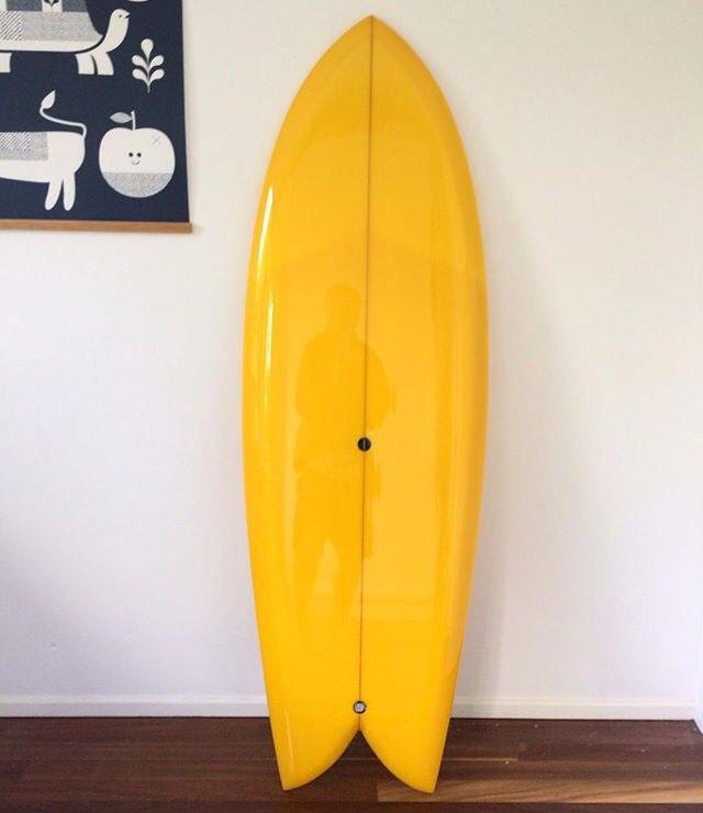 Golden yellow twin fin surfboard