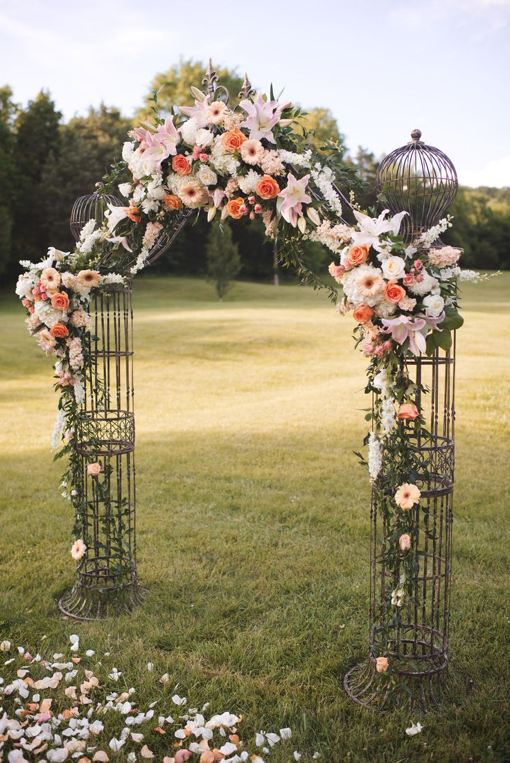 Wedding arch adorned with Peach, blush, and white florals .