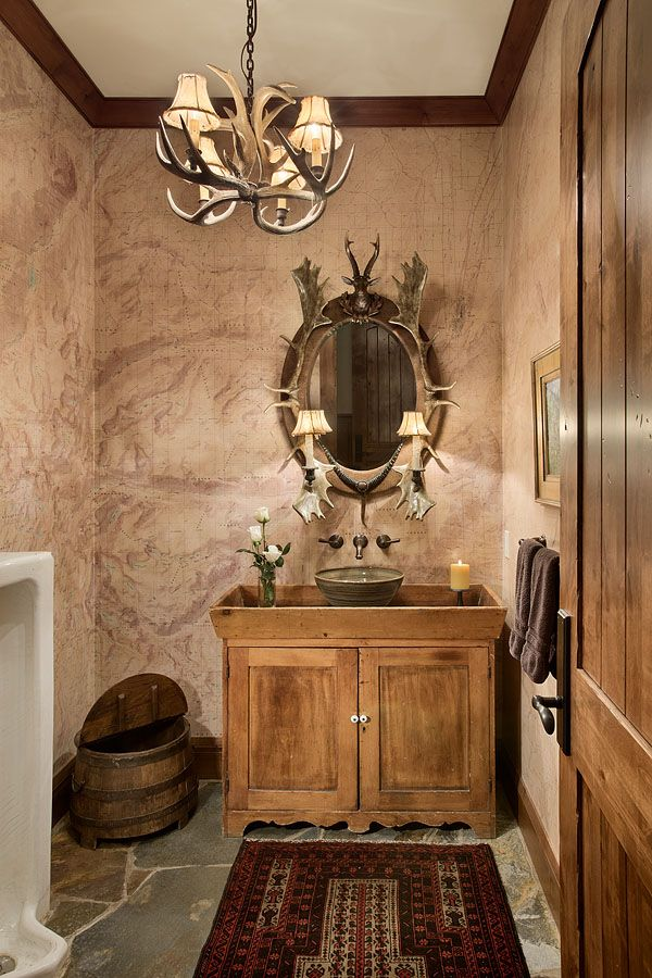 Rustic cabin powder room with antler chandelier and mirror, custom tea stained topo map wallpaper, stone floor, and vintage urinal.