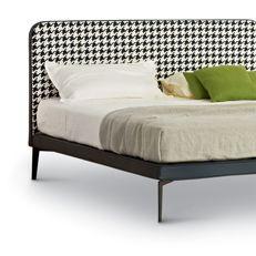 Il letto Suite ha testata imbottita in tessuto con il bordo in pelle e dei piedini in metallo verniciato nero. La testata è ritmata dal gioco di pannelli di diverse misure che danno vita a un letto pratico e di grande eleganza.