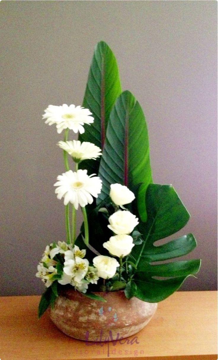 3 gerberas blancas, 4 rosas blancas, astromelias blancas (un grupito), hoja piñanona, y 2 hojas verdes de follaje.