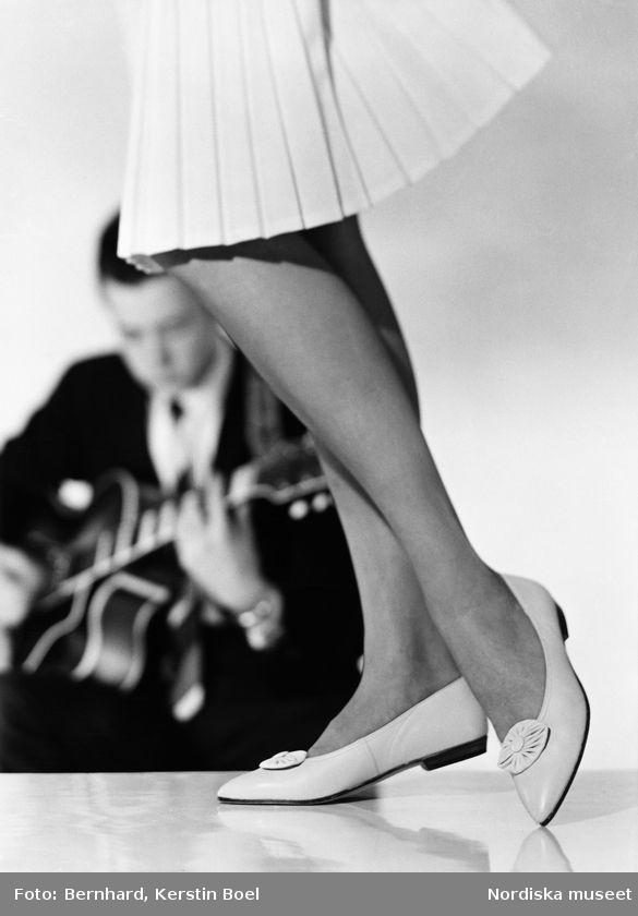 Veckad, vit kjol, platta damskor i skinn och man på gitarr i mörk kostym. Foto: Kerstin Bernhard, 1960/1965