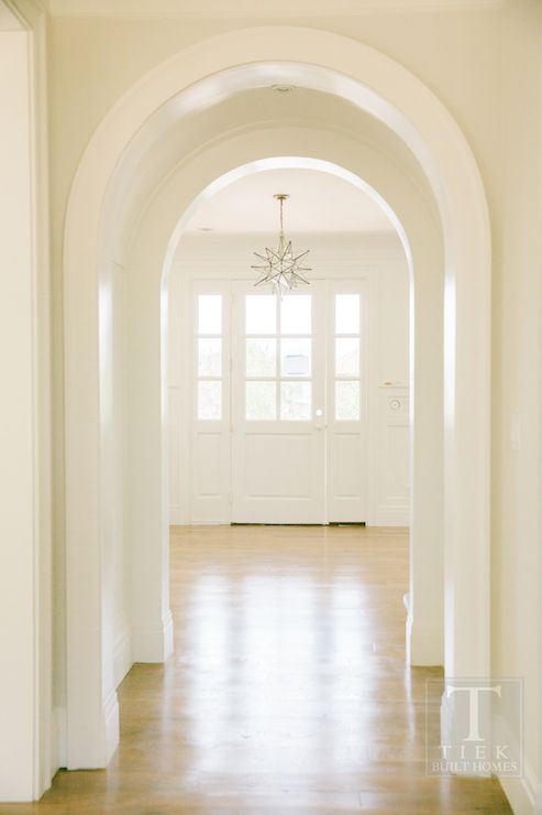 Tiek Built Homes - entrances/foyers - Benjamin Moore - Simply White - arched doorway, archway, foyer archway, entryway arch, light hardwood floors, white front door, glass paned front door, sidelights, front door sidelights, moravian star pendant, star shaped pendant light, arched hallway, curved door moldings,