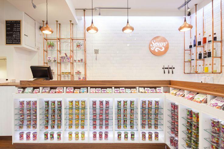 Spun, negozio di caramelle a Londra. La struttura degli scaffali a parete è costituita da tubi di rame. I lampadari, rifiniti in rame, ricordano una goccia di cioccolato fuso.