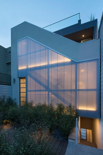 The wall of polycarbonate panels on the south side of the house, where the front door is located, filters heat and blocks views from a guest cottage across the small courtyard. Because the street-facing side has all the views toward downtown San Francisco, Marlatt organized the stairs on this courtyard-facing side.