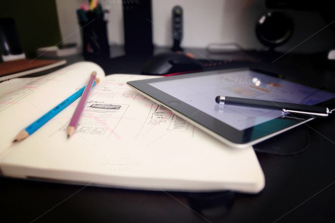 Designer workspace with tablet, stylus pen, pencils and sketches in a notepad.
