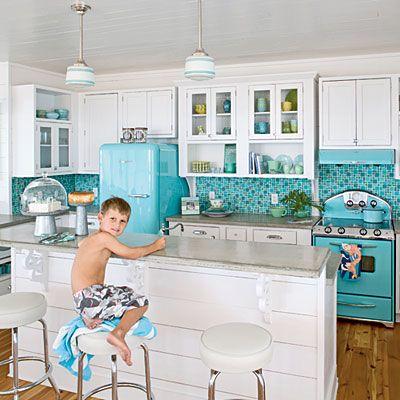 Kitchen •~• Vintage Vacation •~•  Though usually reserved for fabrics and surfaces, color can also come to life through appliances and accessories. A vintage-style cooktop and refrigerator, plus punchy turquoise tiles, stock this beach house kitchen with an ultimate easy-living vibe.
