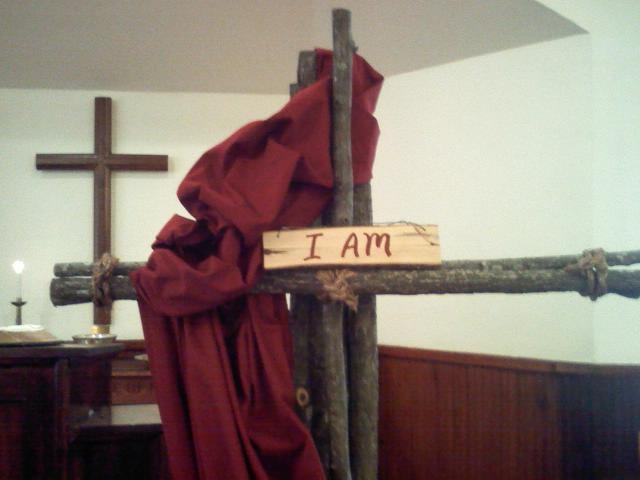 """Close-up of the """"I am"""" cross. Note that the trinity is also represented here -- the """"I am"""" words originally spoken by God the Father, red for the Holy Spirit, and the cross for Jesus crucified in the flesh. I love that the cross is made up of multiple bars tied together. They hint of community...God is three in one, one in three. God says """"let us create humankind in our image"""" and we too are meant to be bound together, a community."""