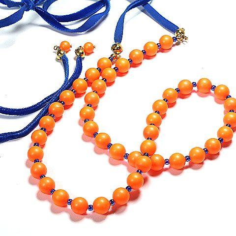 Lange Halskette aus neon-orangenen Glaswachsperlen (8mm Ø) von SWAROVSKI- ELEMENTS und einem blauen Samtband als Verlängerung. Diese Kette kann kurz am Hals getragen werden oder lang (bis zu 1m). Um die Kette zu verschließen, wird das Samtband zur Schleife gebunden.
