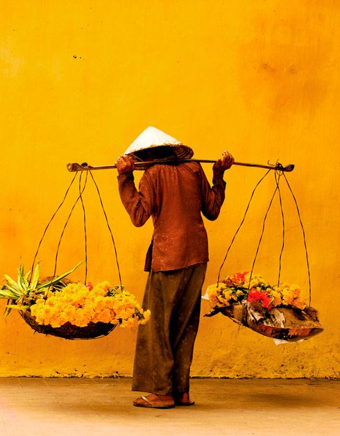 Vietnamese woman selling flowers on the streets of Hoi An Vietnam.