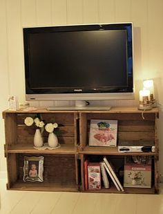 Wooden crates for a tv stand? I would store our photo albums underneath and add curtains