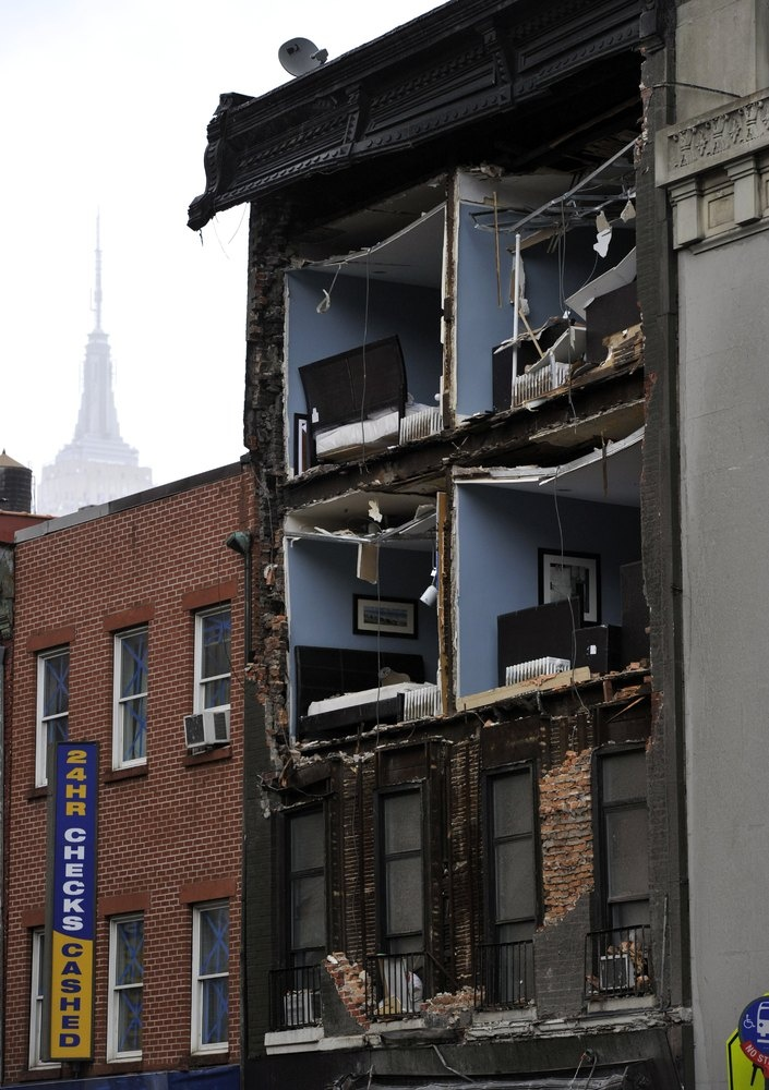 The Empire State Building towers in the background of an apartment buliding in Chelsea, New York City, with the facade broken off October 30, 2012 the morning after Hurricane Sandy.  AFP PHOTO / TIMOTHY A. CLARY (Photo credit should read TIMOTHY A. CLARY/AFP/Getty Images)