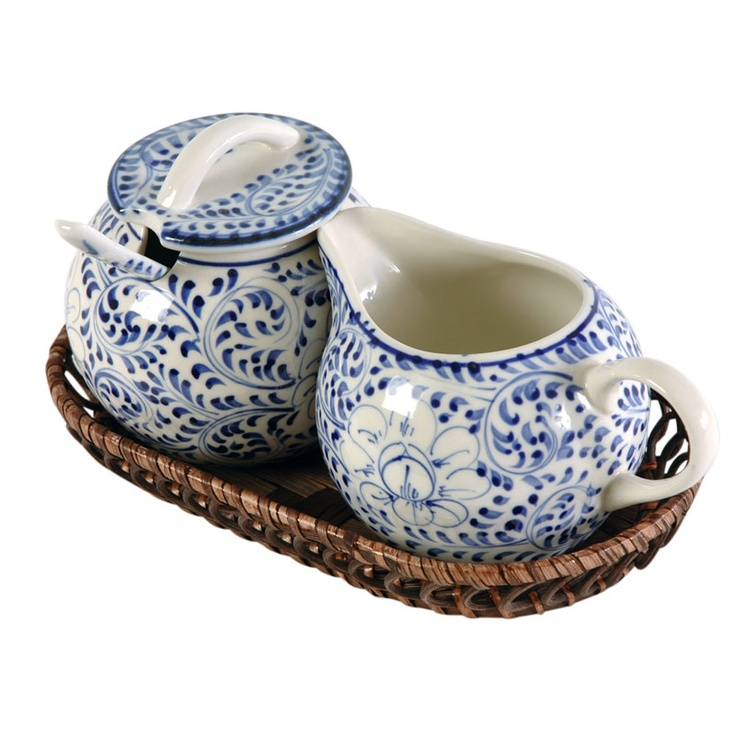 A perfect pair! This blue and white sugar bowl and cream pitcher fit snugly together in their woven bamboo basket. The notch in the sugar bowl lid makes room for the lip of the jug. The delicately-sized sugar spoon rests in the recess of the bowl. Handmade in a traditional style influenced by Ming China.