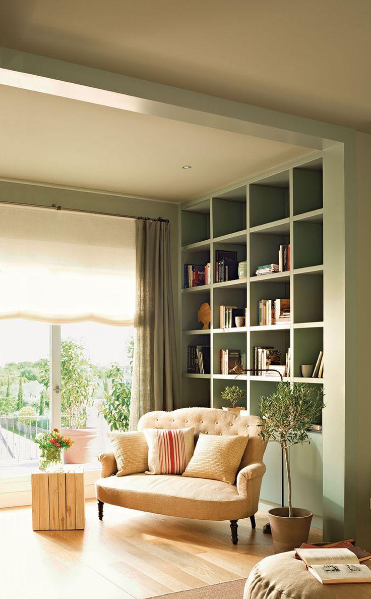 Biblioteca con una librería verde hasta el techo con un sofá beige con cojines de diferentes estampados_00342795