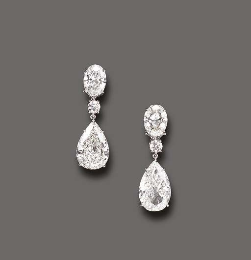 AN ELEGANT PAIR OF DIAMOND EAR PENDANTS Each pear-shaped diamond, weighing approximately 5.07 or 5.51 carats, suspended by a circular-cut diamond spacer, to the oval-cut diamond surmount, weighing approximately 1.80 or 1.87 carats, mounted in platinum