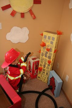 """Fire truck birthday party. Everything built from cardboard boxes and painted with acrylic paint. Vacuum hose hooked up to """"hydrant""""."""