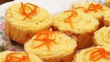 Billedet viser appelsin-cupcakes pyntet med smørcreme og lidt revet appelsinskal.